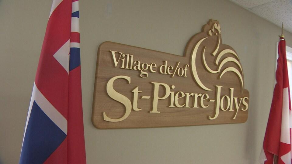L'emblème du village de Saint-Pierre-Jolys, qui représente un coq stylisé, est encadré par les drapeaux officiels.