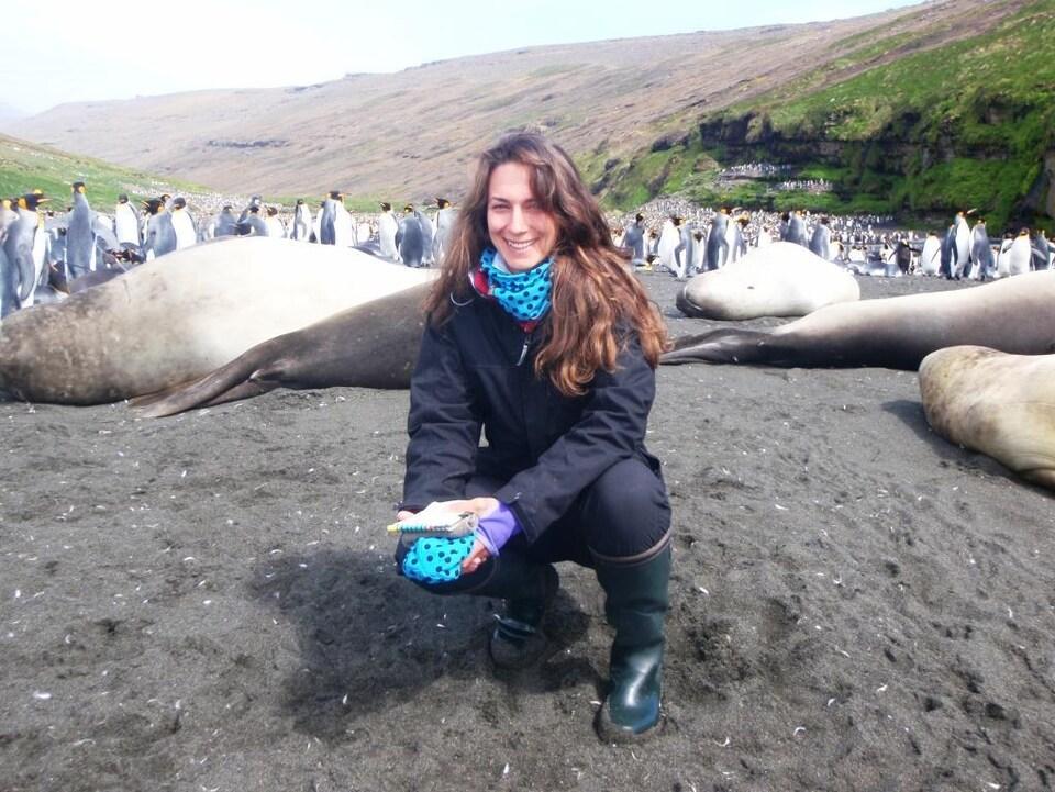 Émilie Lefol devant un groupe de manchots sur l'île de la Possession dans l'Archipel de Crozet en Antarctique