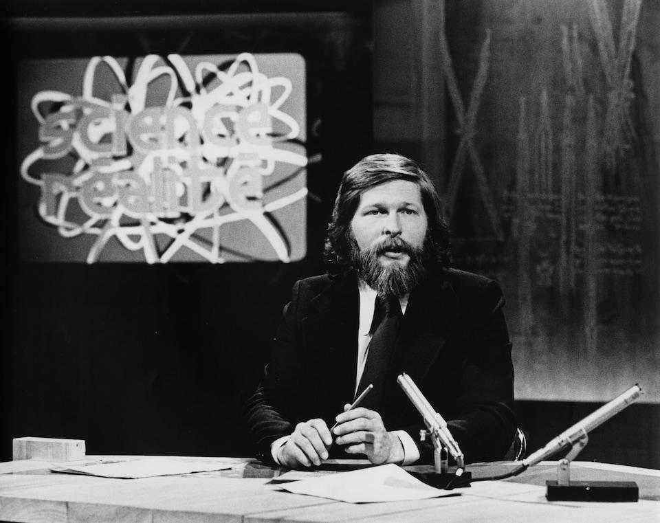 Dans un studio de télévision, l'animateur Joël Le Bigot est assis à une table surmontée d'un micro. En arrière-plan, le titre de l'émission «Science Réalité» apparaît dans un écran sur le mur.