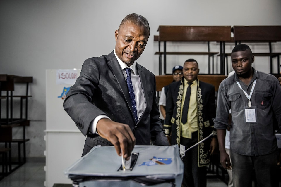 Un homme dépose un bulletin de vote dans une urne.
