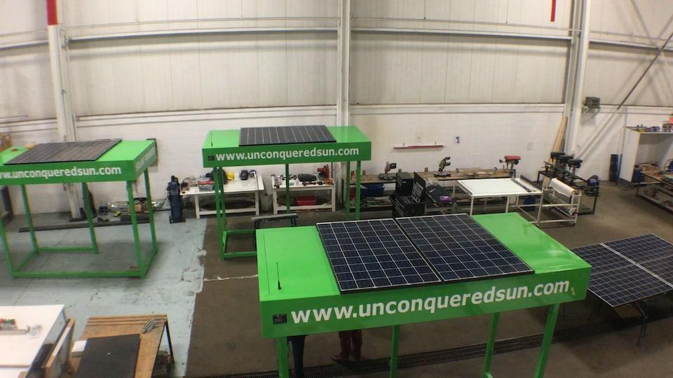 Trois abribus verts avec des panneaux solaires sur leur dessus sont photographies en contre plongée dans un atelier.