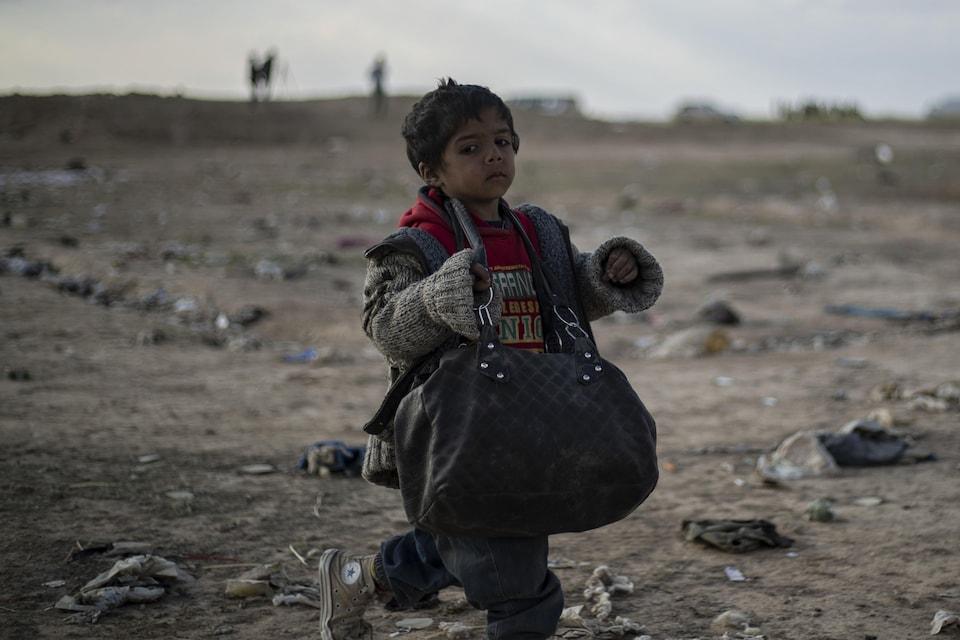 Un enfant marche seul dans une zone de guerre et porte un sac à bandoulière.