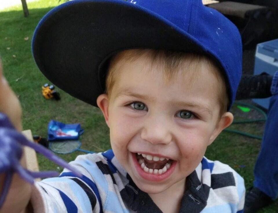 Photo d'un garçon qui sourit portant une casquette bleue.