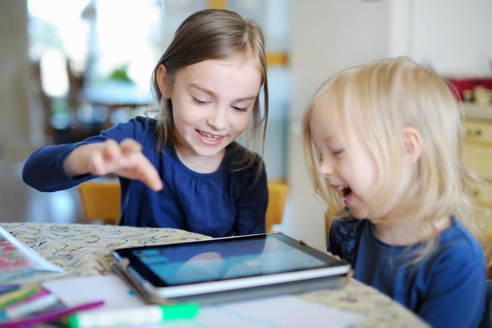 Deux fillettes rient et jouent avec une tablette.