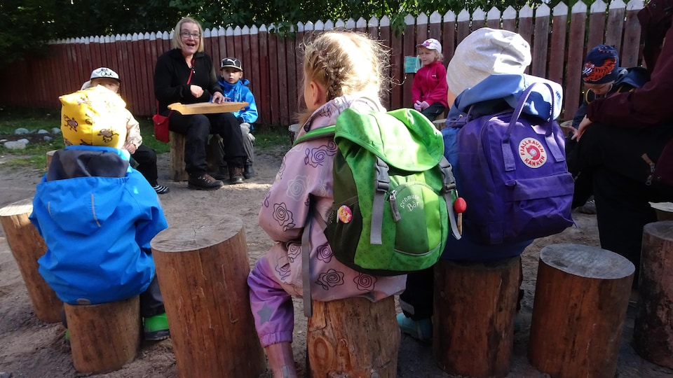 Des enfants assis sur des bûches écoutent leur enseignante.