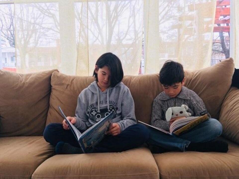 Les deux garçons lisent côte à côte sur le divan.