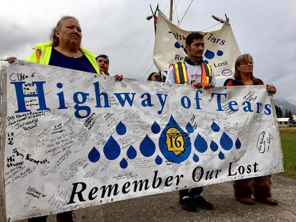 Trois personnes tiennent une grande affiche qui appelle à ne pas oublier les victimes de la route des larmes. D'autres personnes les suivent.