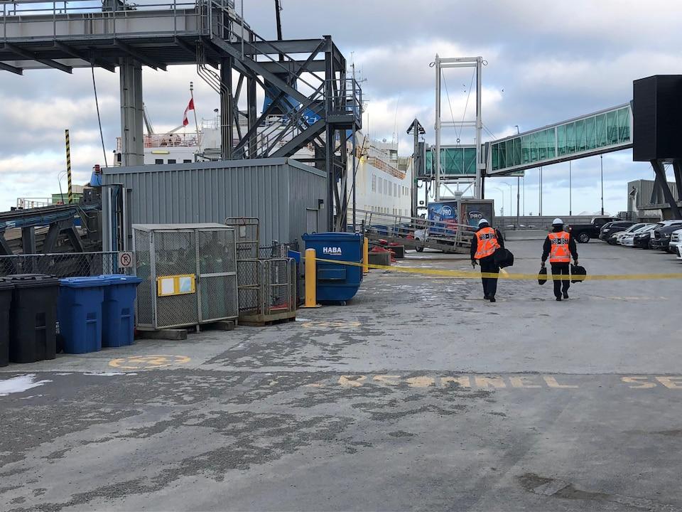 Deux enquêteurs du BST marchent au quai de Matane, alors qu'on voit le traversier Apollo derrière des structures de métal.
