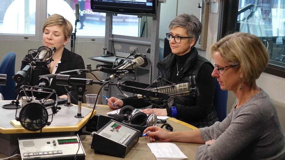 Trois femmes devant des micros dans un studio de Radio-Canada.