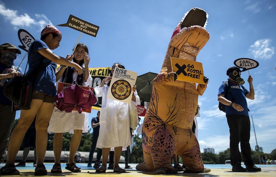 Des manifestants tenant des pancartes, dont l'un d'eux, habillé en dinosaure, tient une pancarte Go fossil free (Finissons-en avec les énergies fossiles).