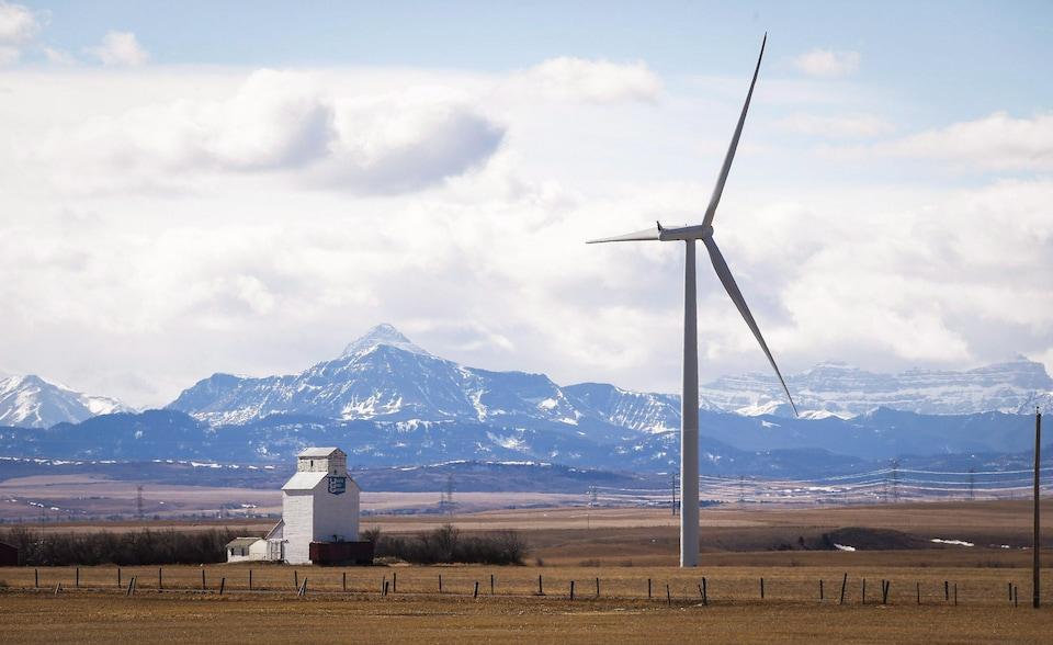 Paysage du sud de l'Alberta avec une éolienne en premier plan à côté d'un ascenseur à grain et les montagnes Rocheuses en arrière-plan