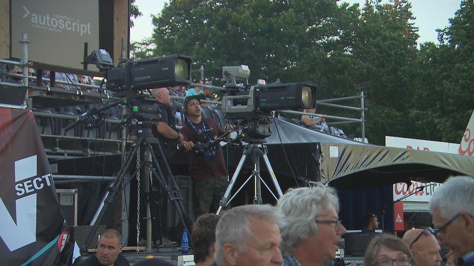 Des hommes discutent derrière deux caméras.