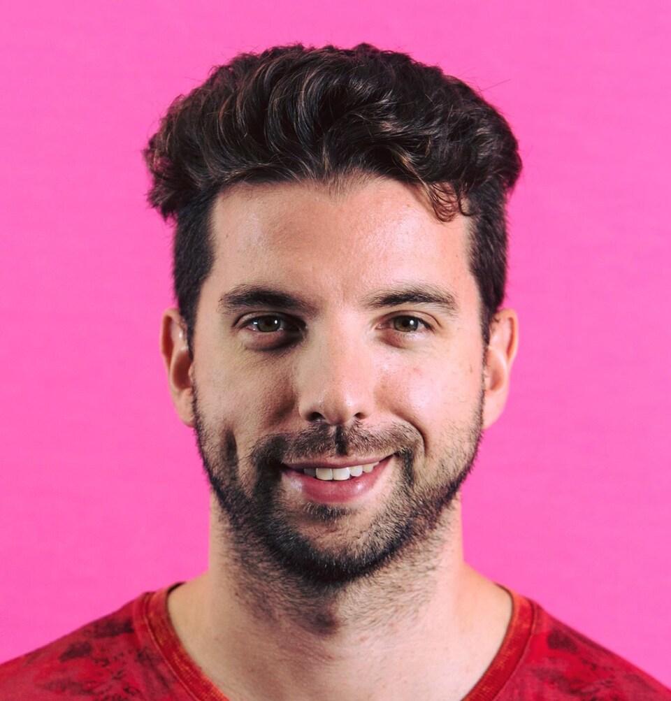 Un homme pose devant un fond rose. Il est brun et a une légère barbe. Il sourit.