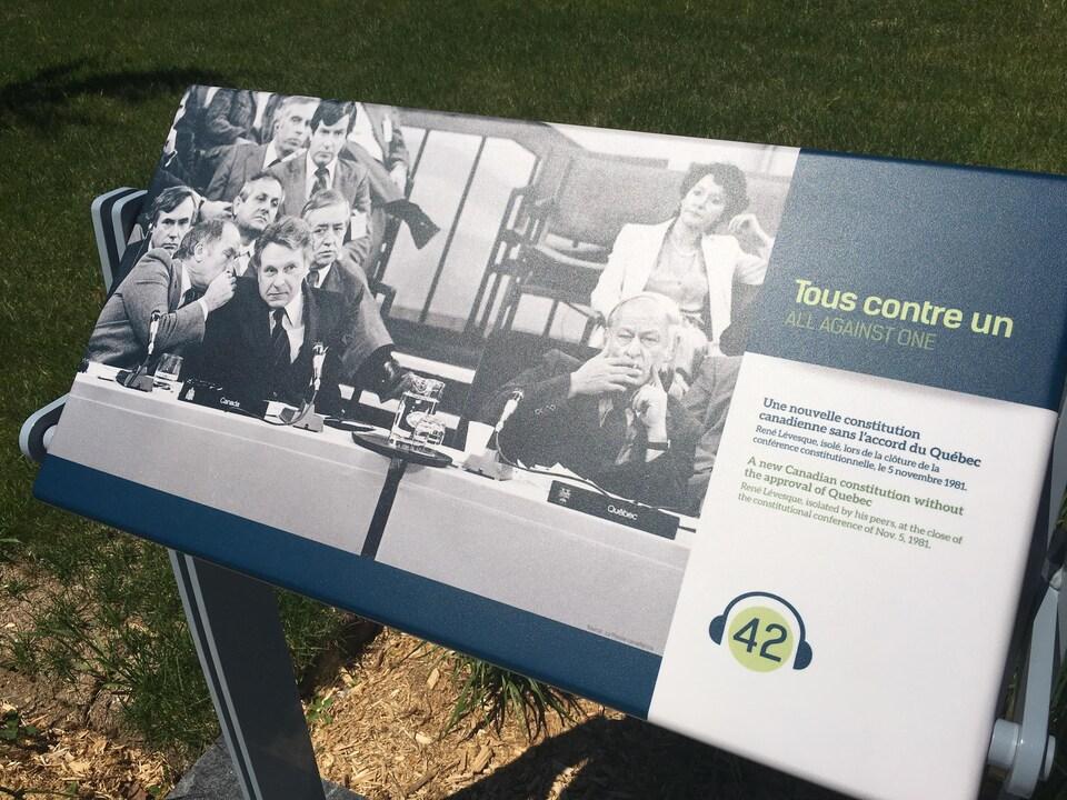 Un panneau montre René Lévesque lors de la conférence constitutionnelle en 1981. Le panneau est positionné à l'extérieur, dans un trajet thématique à plusieurs volets portant sur la vie de cet homme politique.