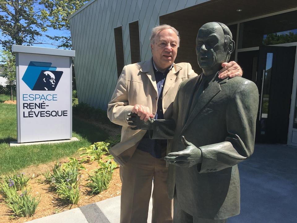 Louis Bernard pose avec une statue de René Lévesque à l'extérieur d'un bâtiment. Il s'agit de l'Espace René-Lévesque à New Carlisle.