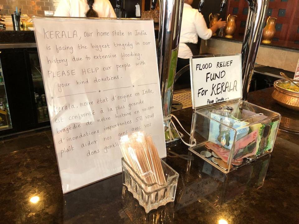 Un message pour les clients du restaurant et une boîte pour déposer des dons.