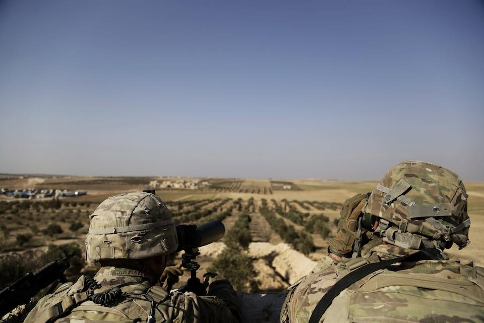 Deux soldats américains installés en hauteur regardent au loin, à l'aide de jumelles, le village de Manbij, au nord de la Syrie.