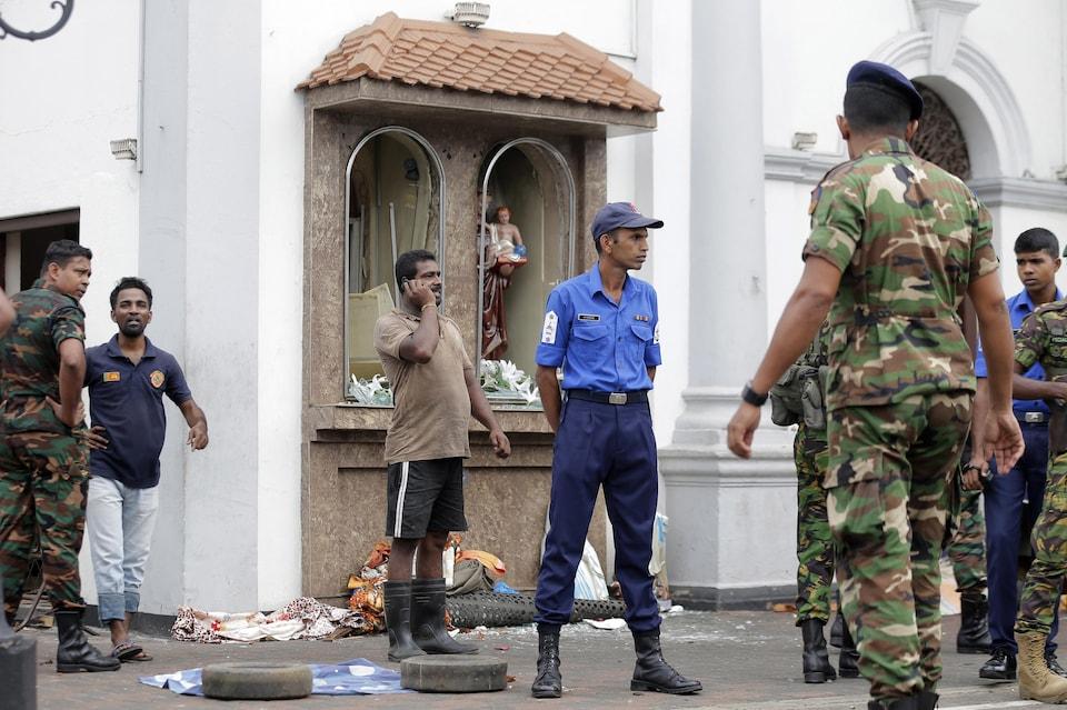 Deux personnes qui viennent d'échapper à une explosion dans une église sont entourées de policiers.