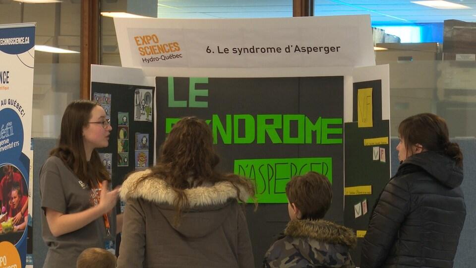 Une participante présente son projet sur le syndrome d'Asperger devant son présentoir