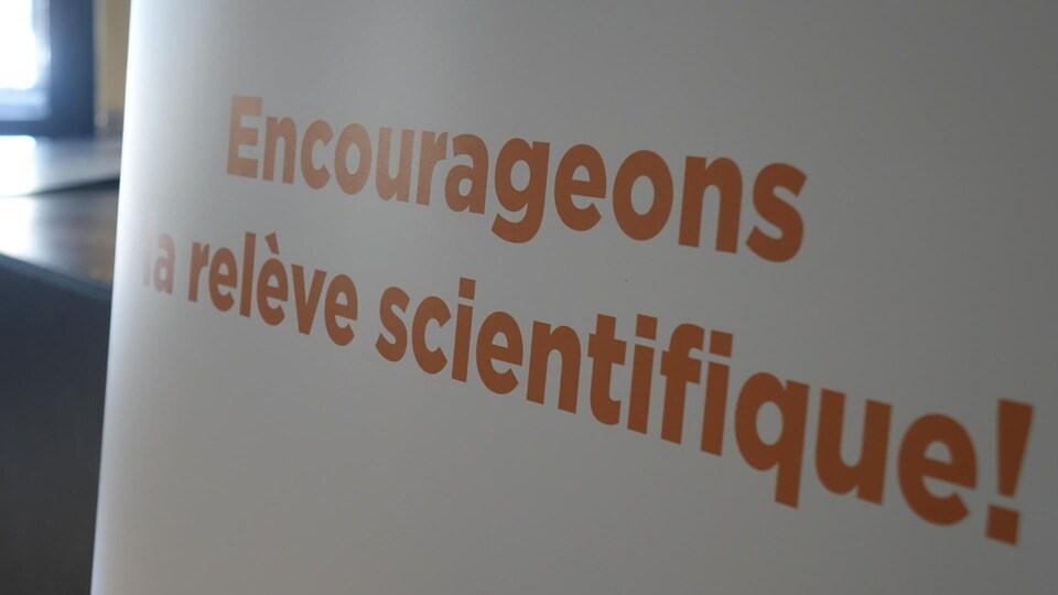 Une affiche sur laquelle on peut lire «Encourageons la relève scientifique»