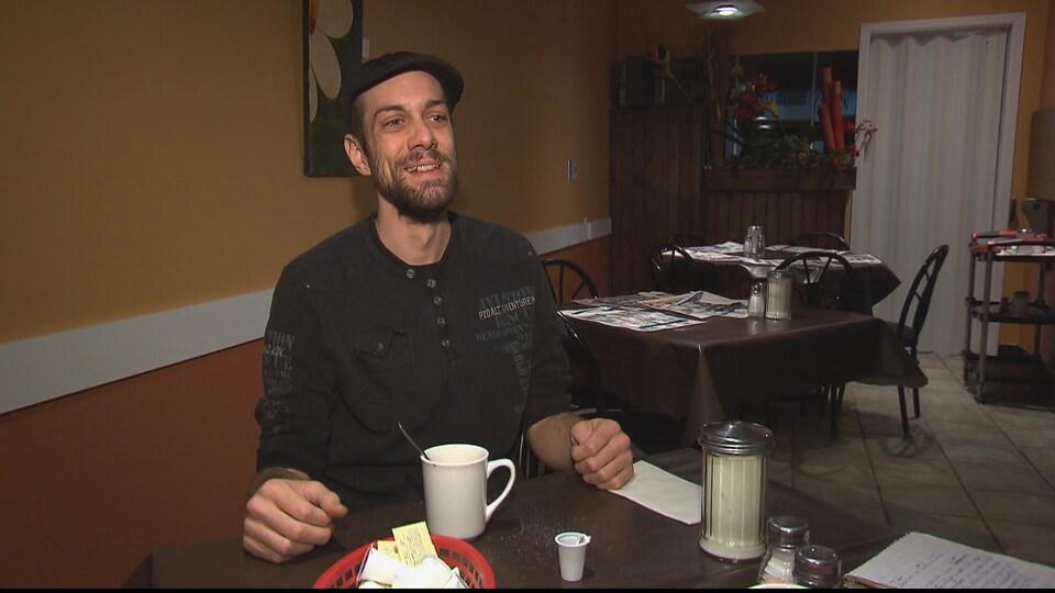 Un homme assis à une table dans un café. Il sourit.