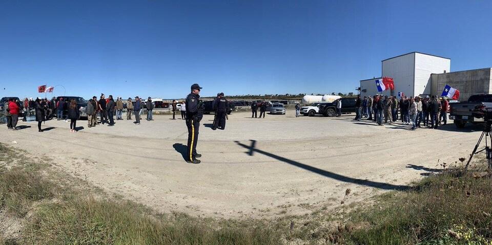 Deux groupes de gens brandissant des drapeaux et quelques policiers entre les deux.