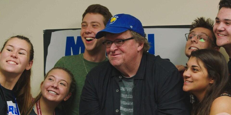 Michael Moore entouré de plusieurs jeunes.