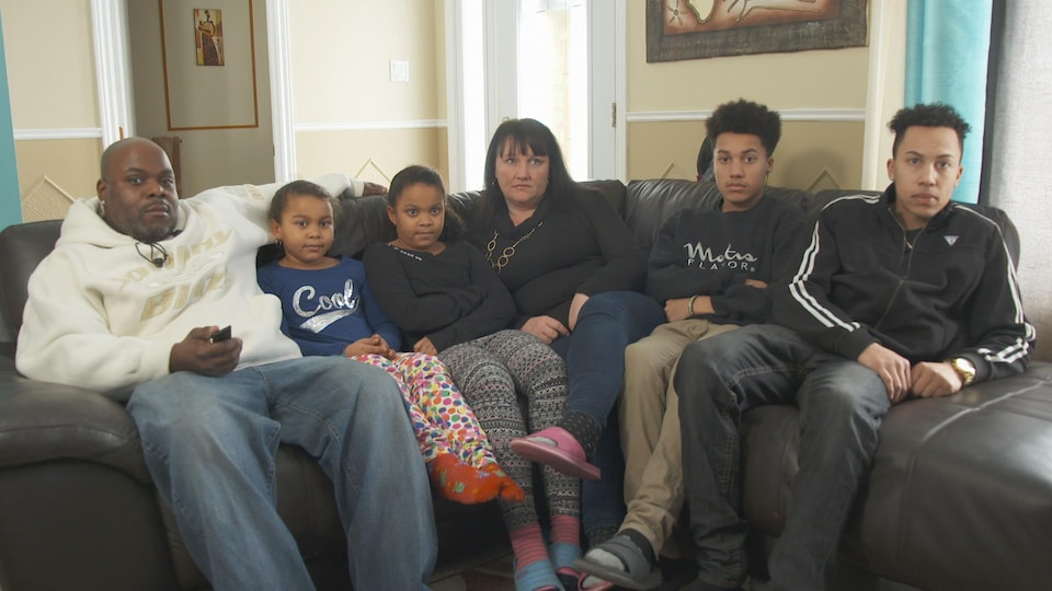 Les deux parents avec leurs quatre enfants, assis sur le divan du salon.
