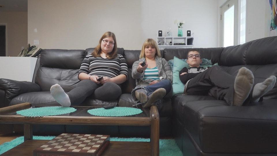 La mère et ses deux enfants sur le divan du salon.