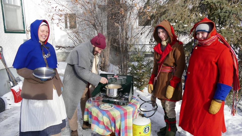 La famille des Voyageurs officiels du Festival du Voyageur, dehors en hiver autour d'un petit poêle sur lequel Christian fait cuire de la soupe aux pois. Ils sont habillés en costume d'époque.