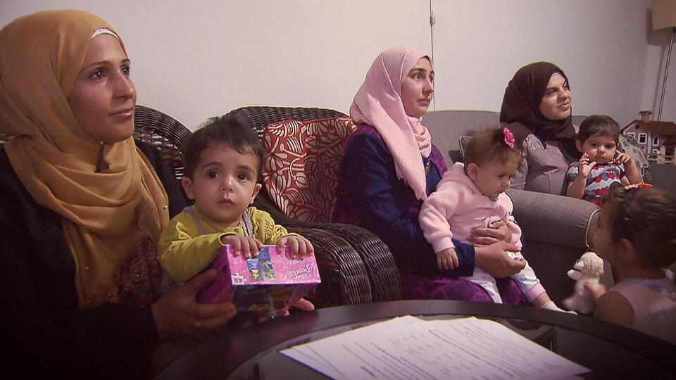 Trois femmes sont assises sur des fauteuils avec leurs petits enfants dans les bras; sur une table au premier plan il y a un papier.