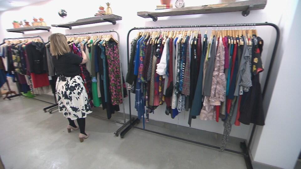 La jeune entrepreneure place des vêtements dans son commerce, la boutique Caprice.