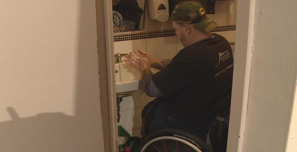 Un homme en fauteuil roulant se lave les mains dans la salle de toilette étroite d'un café