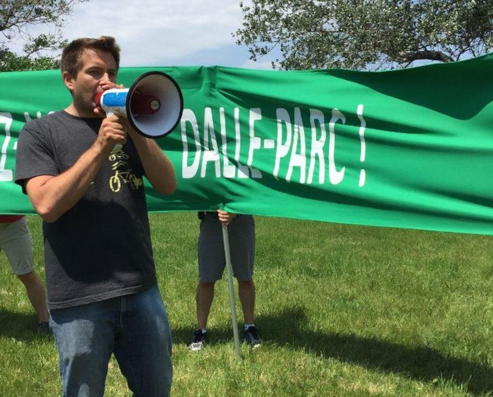 Félix Gravel, co-porte-parole de Piétons Québec, s'adressant à la foule à l'aide d'un porte-voix lors d'une manifestation pour une dalle-jardin sur le nouvel échangeur Turcot, à Montréal, avec une banderole verte disant «dalle-parc» derrière lui.