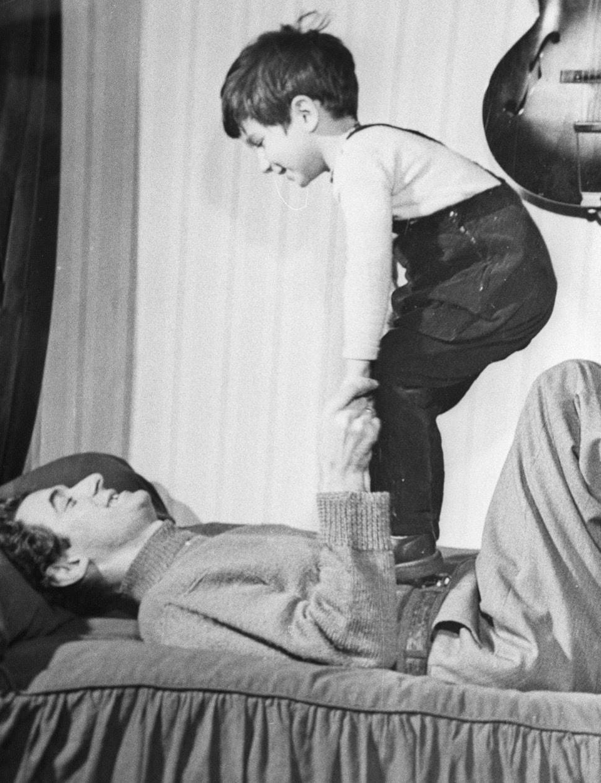 Félix Leclerc et son fils, Martin. Le chanteur dans la trentaine est couché et debout sur lui, son fils.