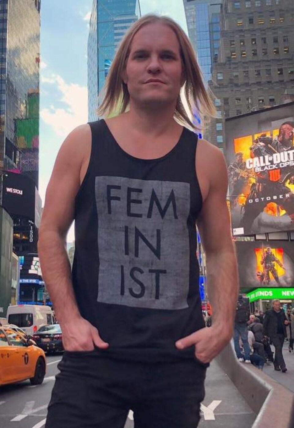 Un homme à la carure sportive et à l'attitude franche photographié à contre-jour dans une rue de New-York. Sur son débardeur le mot «feminist» peut se lire en lettre capitale.