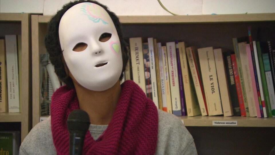 Une femme membre du Collectif des femmes sans statut de Montréal parle dans un micro et soutient que les femmes sans-papiers sont plus vulnérables que les hommes.