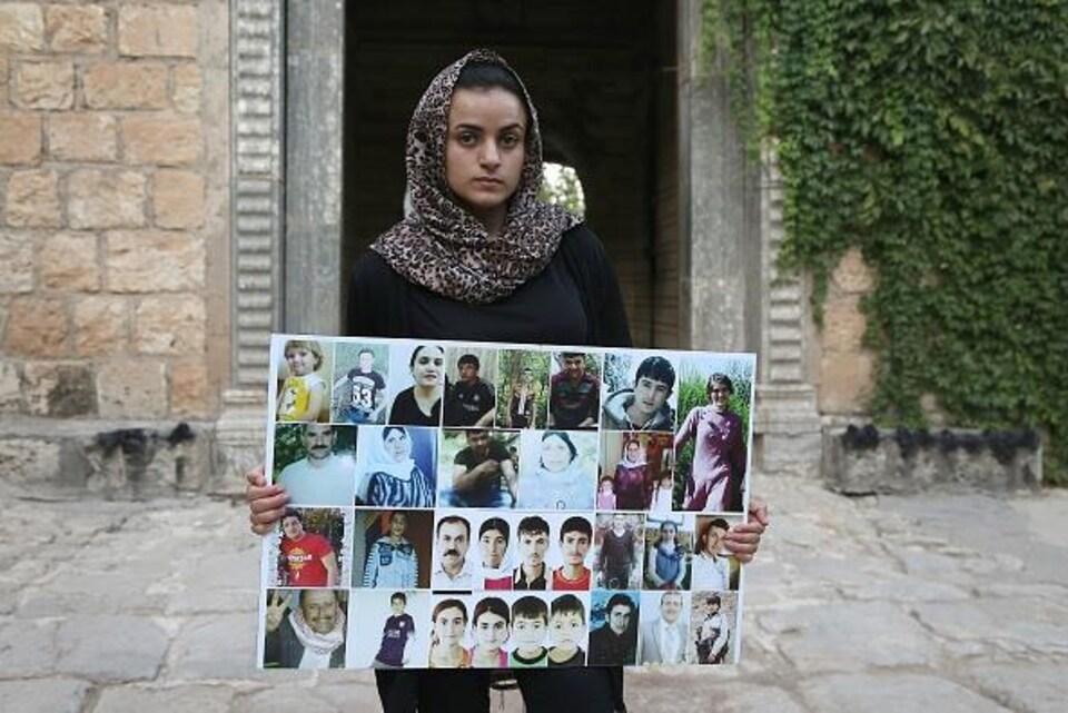 Ashwaq Haji, une femme yézidie, qui aurait été utilisée comme esclave sexuelle par le groupe de l'État islamique, tient des portraits de victimes djihadistes de son village de Kocho près de Sinjar.