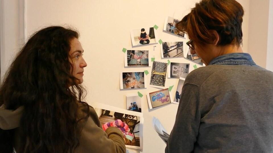 Deux femmes discutent et regardent les photos collées au mur.