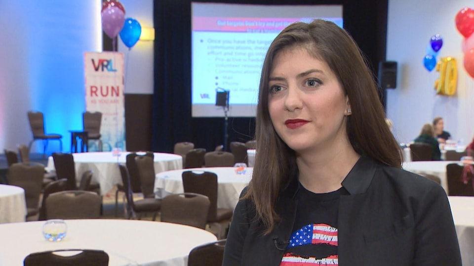 Erin Vilardi porte un veston noir sur un t-shirt aux couleurs du drapeau des États-Unis.