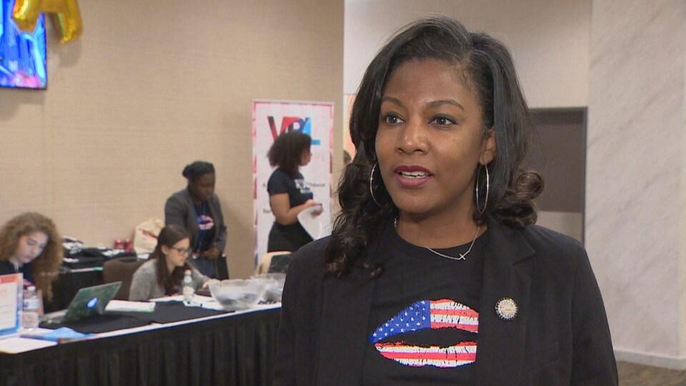 Tishaura Jones porte un veston noir par-dessus un t-shirt de la même couleur sur lequel est imprimé la marque d'un baiser aux couleurs du drapeau des États-Unis.