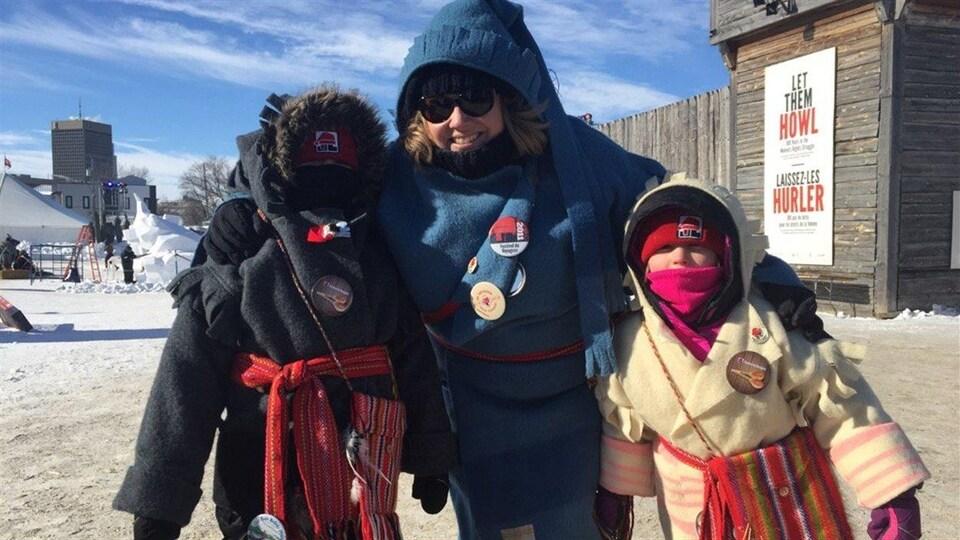 Une femme et deux enfants devant le Fort Gibraltor au Parc du Voyageur.