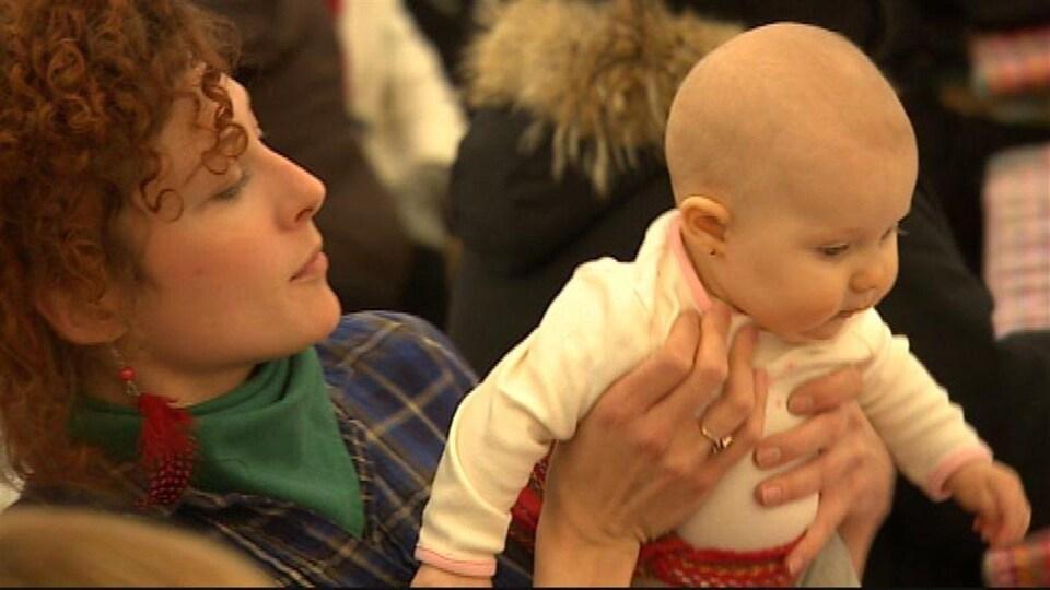 Une mère et sa jeune festivalière, laquelle porte la ceinture fléchée, s'amusent dans une des tentes du Festival du Voyageur le 23 février 2014.