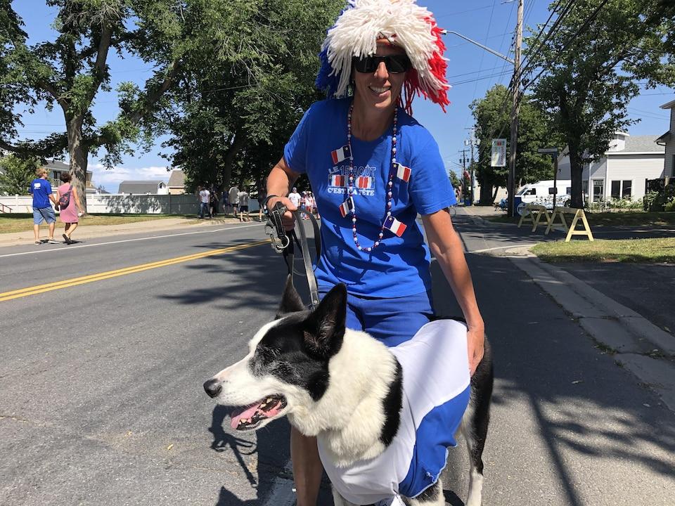 Une personne portant des décorations de la fête de l'Acadie et son chien.