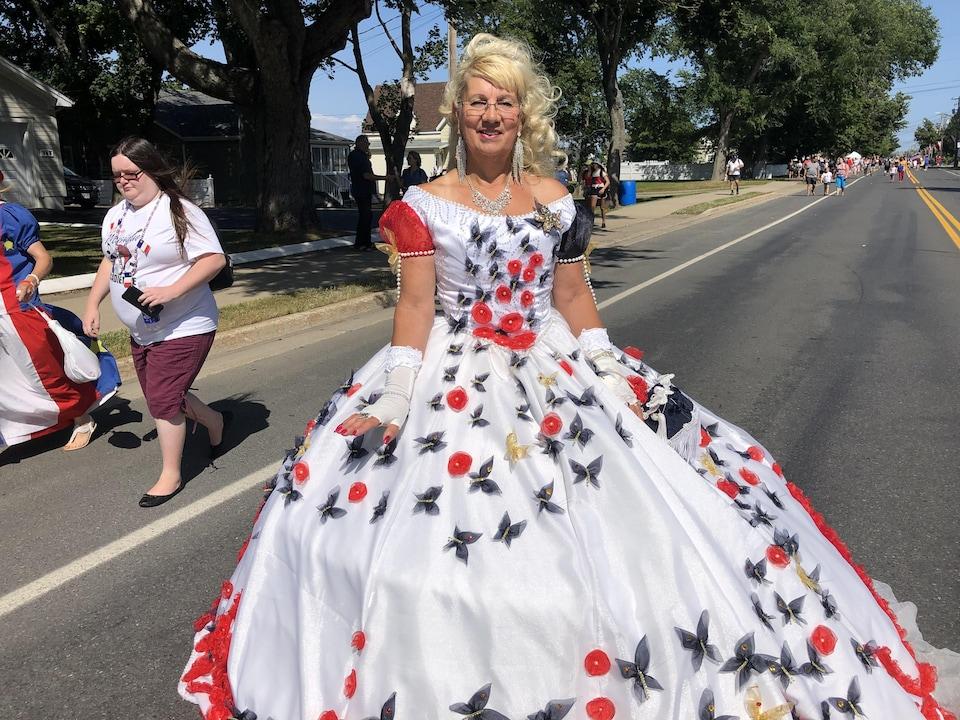 Une femme photographiée dans la rue porte une élégante robe blanche décorée de fleurs rouge et de papillons.