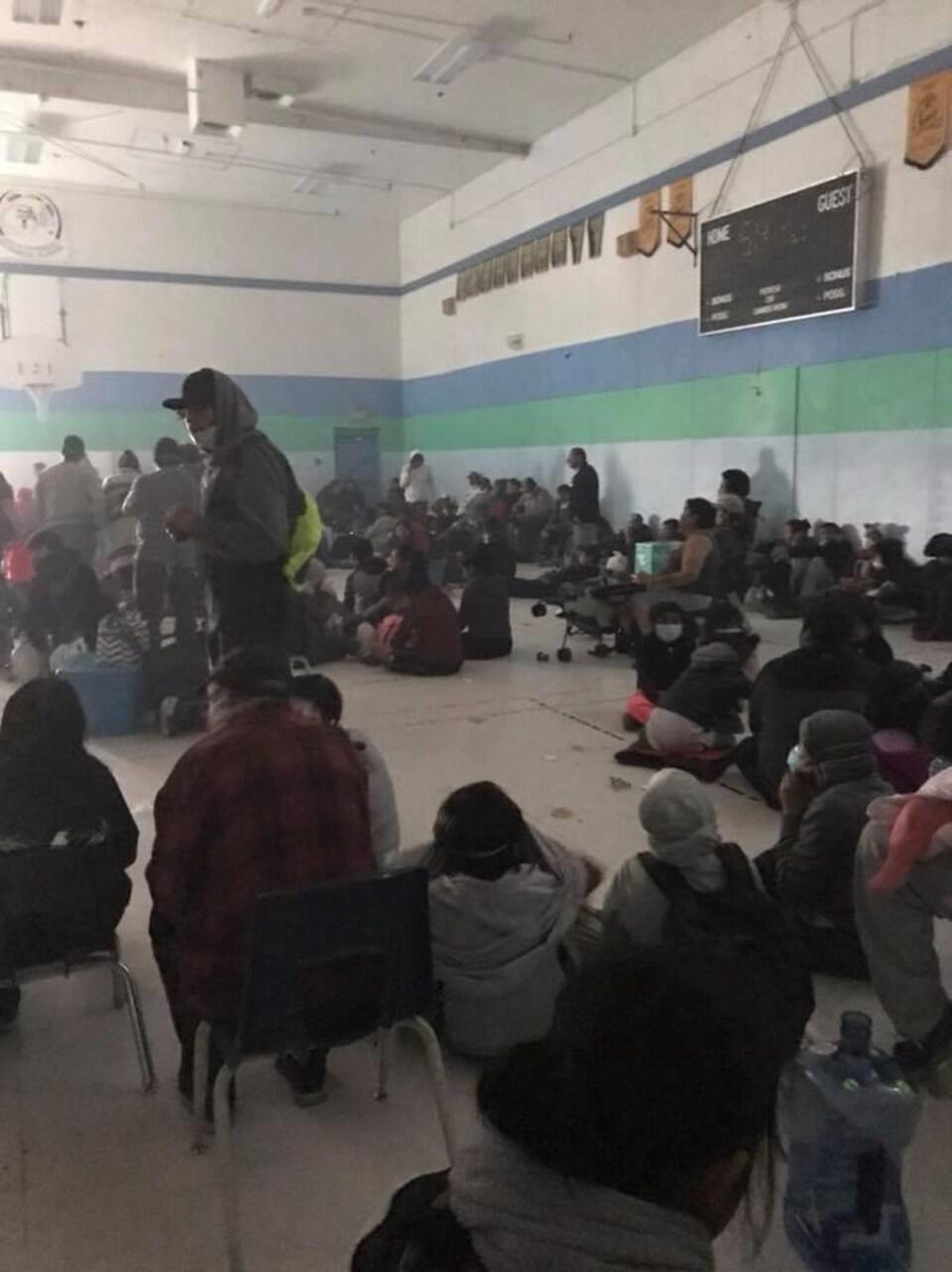 Une quarantaine de personnes dans un gymnase enfumé.
