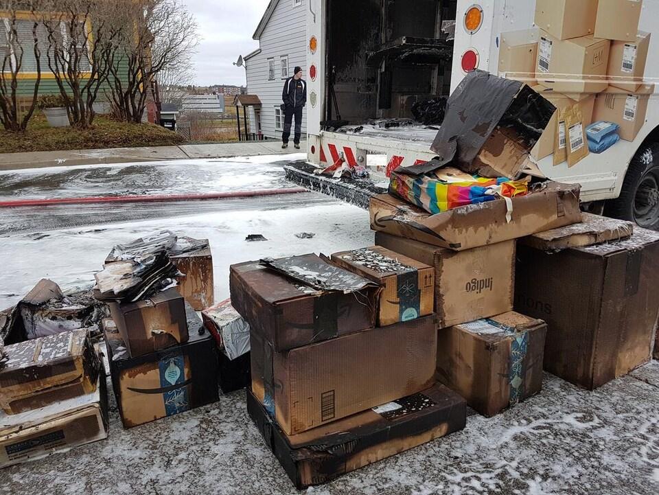 Des colis en mauvais état visiblement trempés sont empilés sur une chaussée enneigée près d'un camion de la poste.