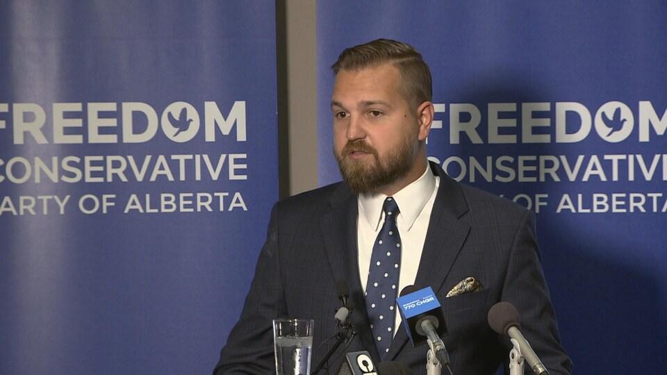 Vue sur un homme avec une barbe. il porte un veston. Il est debout et parle devant des micros.