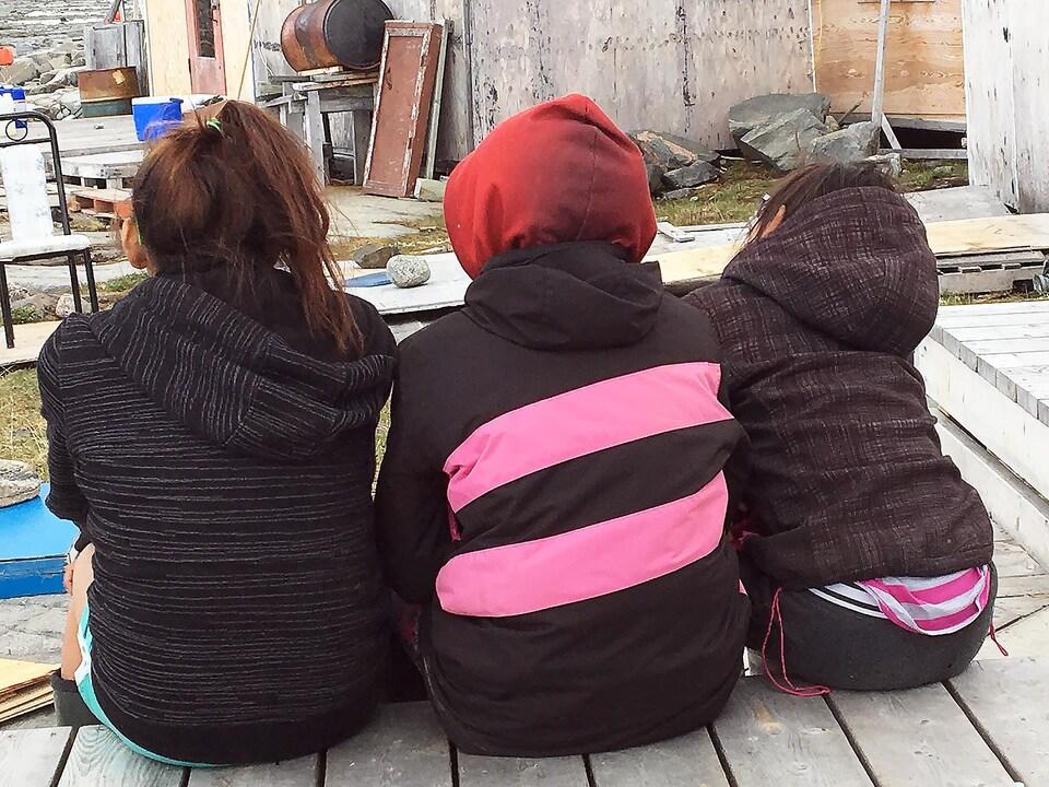 Des filles assissent une à côté de l'autre