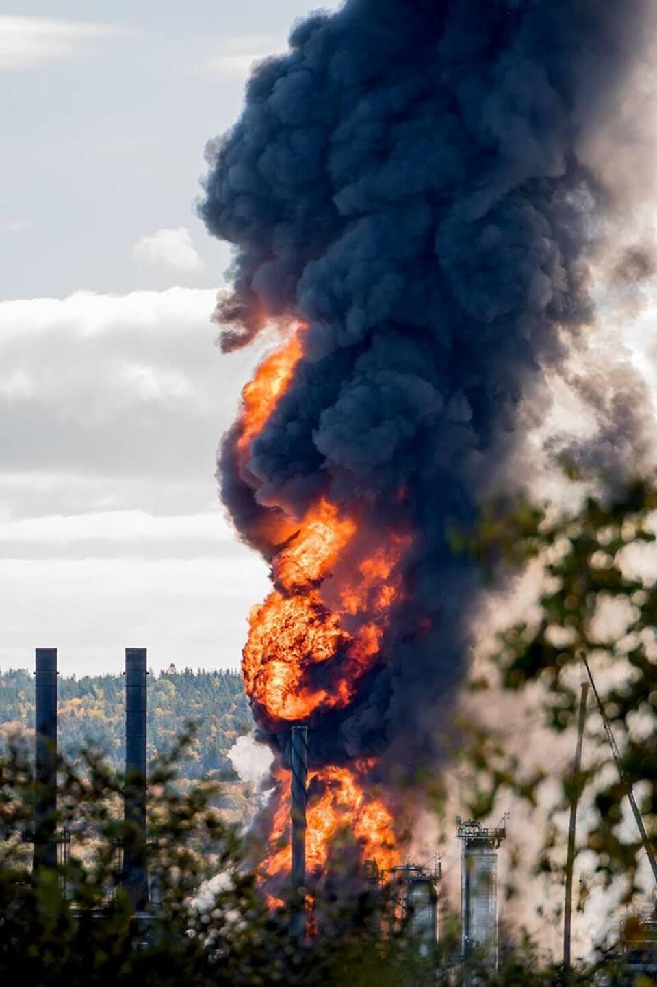 Une gerbe de flammes s'échappe de la raffinerie.